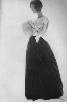 November Harper's Bazaar, 1956    Evelyn Tripp is wearing a long evening skirt, its fashion beautifully accounted for in amber velvet, spilled out below a white satin blouse, by Norman Norell.
