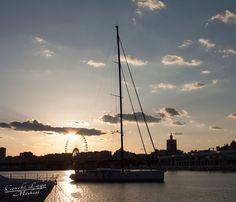 Atardeciendo en el Muelle Uno de Malaga, un velero cruzando con la ya emblematica noria dibujando el fondo