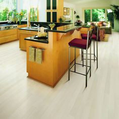 this whitewashed beech laminate floor looks gorgeous with all the greenery peeking through the windows