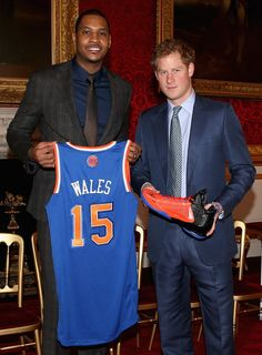 Carmelo Anthony Photos - Prince Harry is presented with a basketball shirt and size 15 basketball shoe by NBA All-Star Carmelo Anthony during a Coach-Core Graduation event at St James's Palace on January 14, 2015 in London, England. The Coach Core model, a year's apprenticeship, aspires to produce well qualified sports coaches to work in the community. The apprentices learn technical sport skills alongside an inclusive and holistic approach to coaching, with an emphasis on employability and…