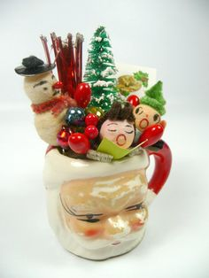 A cute little Christmas decoration made with all vintage findings... A vintage tiny Santa mug is stuffed full of retro holiday goodies including vintage