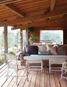 ❤ Porch- Life changes pace on a porch sheltered by pine beams. A living and dining areas allow you to enjoy the beautiful scenery. Rattan sofa, Isabel López-Quesada, wicker chairs and a bench French bric Hilary Batstone recycled wood.