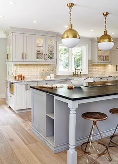 Arteriors Wyndham Stools sit on slightly stained wood floors in front of a gray island with turned legs accented with cookbook shelves and a black marble countertop finished with an integrated cooktop lit by Hicks Pendants.
