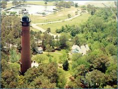 "The Currituck Beach Lighthouse Located in Corolla, NC, it was built to fill the last remaining ""dark spot"" of the NC coast between Bodie Island to the south and Cape Henry, VA to the north. Many ships foundered in the 80-mile darkness between the two lighthouses, but this lighthouse, with its beam visible for 18 miles, solved the problem. To distinguish it from other regional lighthouses, it was left unpainted in natural red brick."