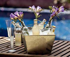 Nada de isopor! Para manter as bebidas geladas, foi usada uma cesta galvanizada com gelo. As garrafas de refrigerante se misturam a outras com flores. Ideia da paisagista Célia Alves