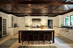 Larchmont Tudor - Allen Ross Architecture. Contrast between dark wooden ceiling and kitchen isle vs all white cabinets is amazing!