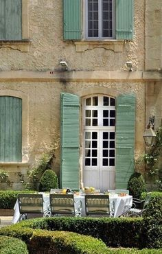 Green shutters and trimmed boxwood hedges in Provence, France.