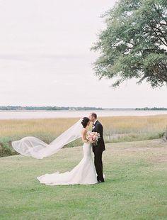 Michelle & John pose in front of the Ashley River at Lowndes Grove Plantation   November wedding inspiration in Charleston, South Carolina   Photo by Landon Jacob