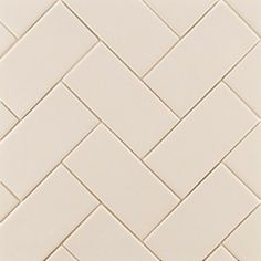 """Herringbone Subway tiles lend themselves to a variety of installations, including this classic herringbone pattern. Shown here, a 3"""" x 6"""" ceramic tile from the Ann Sacks NOW collection in butter cream gloss."""