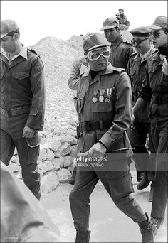 King Hassan II of Morocco (C) followed by Moroccan military officers, in particular General Bennami, the commander of the zone of south of Morocco, (3rd-R) and his son, Prince Moulay Hassan (R), inspects the 'defense wall' in the Boucraa region 16 March 1985.