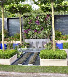 Comme un tableau accroché à la paroi du fond du jardin, le mur végétal est un élément très fort du décor et qui sert de point focal dans ce petit jardin : Les plantes utilisées sont Begonia rex 'Magic Colours', Begonia 'Escargot', Epimedium rubrum, Tiarella 'Braveheart', Ajuga reptans 'Atropurpurea', Lamium 'Beacon Silver' et Viola à fleurs violettes. #mur #végétal #jardin #begonia #epimedium #chelseaflowershow #ajuga #paysagiste