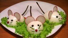 Muisjes van half gekookt ei. Oogjes en neusje van peperkorrels.  Snor van bieslook en oortjes van radijs. Staart weet ik niet. Leuk geserveerd op een blaadje sla.