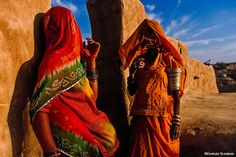 #4 in the series: 'People of the Thar Desert' – Two women converse by the entrance to the courtyard of a house, in a remote 'dhani', a traditional village in the Thar Desert. We photograph the Great Indian Desert and its inhabitants during our Thar Desert Photography Expedition