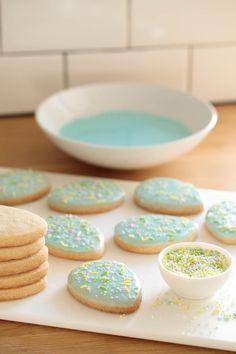 Photo of a white cutting board filled with Spring Shortbread Cookies with a bowl of frosting in the background and a dish of pastel sprinkles in the foreground. Easter Cookies, Easter Treats, Spring Recipes, Easter Recipes, Cookies Et Biscuits, Sugar Cookies, Shortbread Cookies With Icing, Easter Biscuits, Shortbread Biscuits