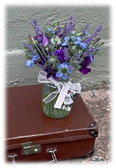 Pretty blue flowers in a jam jar - simple yet beautiful idea for country style wedding decorations! joannetrubyfloraldesign.com