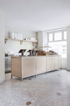 Multidisciplinary studio Frama has finished this bakery in Copenhagen with off-white walls and terrazzo floors, allowing the bread loaves and pastries on offer to take centre stage. Off White Walls, Interior Architecture, Interior Design, Wooden Counter, Terrazzo Flooring, Open Layout, Oak Doors, Large Windows, Danish Design