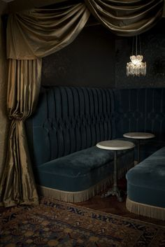 Speakeasy style. Dark blue velvet banquette, lush throw rugs, gold drapes. Perfect color scheme for party.