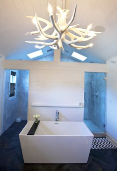 An antler light fixture illuminates a soaker tub