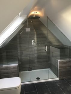 Frameless shower enclosure in gable roof loft conversion.
