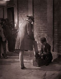 Credit: John Thomson/Hulton Archive/Getty Images A young independent shoeblack shines the boots of a city gent 1877 street life in london