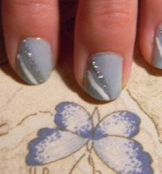 Simple Yet Beautiful!  1. Start by painting your nails light powder blue or any other soft color. Allow to dry.  2. Using silver detailing brush nail polish, create a diagonal line starting at the upper corner of your nail and dragging it down to the center of the tip of your nail.  3. Create a parallel line to the first one this time using white polish and making the line closer to the edge of your nail than the other.  4. Cover with a clear coat and Ta da!