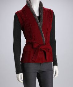 Evoke effortless elegance with a chic, versatile vest. With ever-classy cable knit and a tie at the waist, this sophisticated silhouette takes posh up a notch with a faux fur trim.Measurements (size S): 26'' long from high point of shoulder to hem55% cotton / 45% acrylicMachine wash; tumble dry
