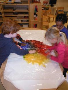 papier op tafel geplakt primaire kleuren erop en stuk plastic erover. wrijven en er verschijnen nieuwe kleuren. plastic eraf en je hebt een mooi schilderij