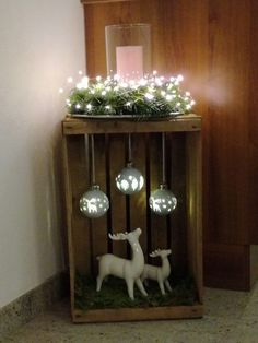Wooden box decorated with lights, reindeer and bulbs for indoor or outdoor Christmas decoration.