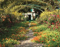 Tour Claude Monet's Gardens Photos | Architectural Digest  The central path in Monet's walled garden, Clos Normand, explodes with jewel-toned nasturtiums during the summer.