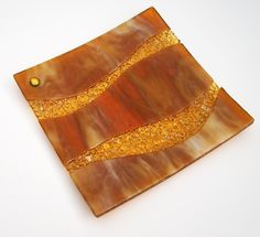 """gold transparent glass, layered w/ amber & cream glass & clear waves of glimmering frit and a gold dichroic accent.   8 x 8 x 1/2"""" square plate.   Bullseye glass 58.00"""