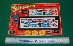 Vintage SUPERMAN - Flying slide tile puzzle by ROALEX, circa early 1960s.  Puzzle is still mounted on original card and is approx 10.5 inches in length.  Great pose of Superman flying through the air.   Puzzle has some melt marks on the black frame and on a few tiles.  VALUE $750.00