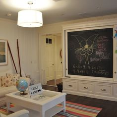 Playroom with sliding chalk board that hides tv.