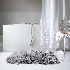 white bathroom with ruffle shower curtain and gray mat