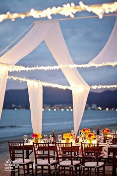 """Nautical wedding reception on the beach - open """"tent"""" with light strands and wooden chairs - very pretty!"""