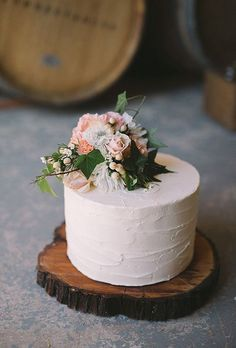 Brides: Single-Tiered Wedding Cake with Flower Cake Topper. A single-tiered wedding cake by Quintessential Cakes, served on a wooden round for a country-chic vibe.