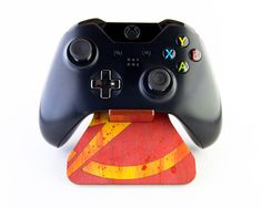 This steuntje, that has been inspired by the famous DC Comics Superhero Flash, is hand painted by me with water based stains. The result is a unique showpiece for storing your controller on and to show you are a fan of Flash. It slides into its final form using the flexible hinge design. It is impossible to lose a part because there is only 1 part to steuntje! → Compatibility This steuntje is compatible with the Xbox One controller. Do you have another controller, take a look at other…