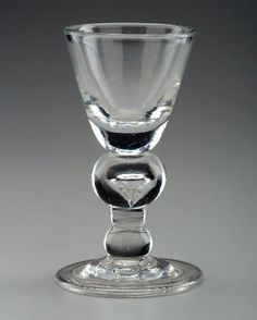 Dram Glass, English, ca. 1700.  Funnel-shaped bowl over large shoulder knop over stem and smaller knop. Conical foot.