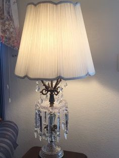 PAIR OF VINTAGE GLASS TABLE LAMPS WITH FOUR ROWS OF CUT GLASS PRISMS. THEY SIT ON BRASS BASES WITH PAW FEET. ONE LAMP HAS A BROKEN ARM THAT NEEDS TO BE REPAIRED AND THE OTHER LAMP HAS A LARGE REPAIR TO THE GLASS. 38H