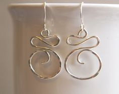 "Simple in their design, but classy in their look, the Sterling Silver Swirl earrings are elegant and light weight! Thick sterling silver is hand formed, textured by hammering. Earrings are 1 1/2"" long"