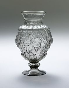 Vase; glass; ovoid; wide spreading neck; ribbed knop and bell-foot; body decorated with bold ribbing above and below; frieze of fruit motifs and lion heads moulded in relief.