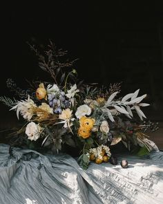 Low lush centerpiece with yellow, golden and gray color palette, ranunculus, pieris, roses, delphinium, with greenery.
