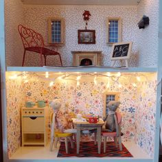 D.Y.I Doll house - Ikea bookcase , patterned paper, windows, fire place, picture frame, chalk board from craft store, big furniture and dolls from Maileg and Christmas lights