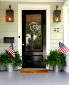 I adore this patriotic 4th of July front door and porch. Door decor using a water-based sharpie paint pen; wipes clean with window spray. Galvanized bucket planters.
