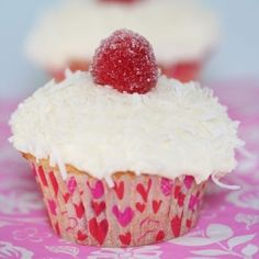 Coconut white cake filled with raspberries and topped with coconut cream cheese frosting, shredded coconut, and a sugar-coated raspberry.