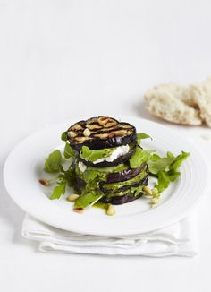Aubergine stacks with pesto, pine nuts and goat's cheese: An easy meal for vegetarians. Simple layers of aubergine, goat's cheese and pesto make a rich but fast meal for two. Sprinkle with pine nuts and serve with crusty bread.