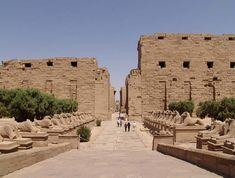 Dromos y primer pilono del templo de Karnak. Esfinges con cabeza de carnero, animal simbólico de Amón, construidas por Ramsés II que unen el templo de Karnak con el de Luxor y con un embarcadero que comunica el templo con el canal que llega del Nilo, para las barcas sagradas durante las fiestas religiosas. Dos pequeños obeliscos, obra de Seti I, preceden al primer pilono de época tardía y posiblemente inacabado, el cual consiste en dos bloques trapezoidales de muros en talud.
