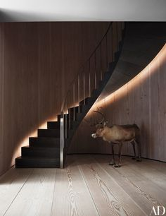 The entrance hall's stone-and-metal floating staircase rises above a taxidermy reindeer.