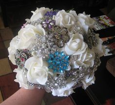 """DIY Brooch Boquet-> Could easily be done in a single afternoon...  30-40 brooches  12 quality silk flowers   2 bunches of silk hydrangea  18"""" 20-gauge green and silver wire  Floral tape  Scissors  Needle-nosed pliers  Wire cutters  Glue gun  Ribbon for handle  Pins  Patience!"""