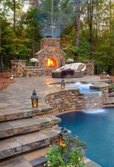 hot tub flowing into pool. outdoor bed by fireplace