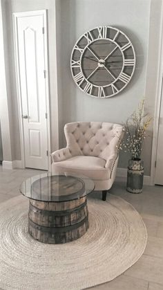 Sitting area , light accent chair , barn wall clock / rustic wall clock / pier 1 , barrle coffee table , jack daniels barrel, whiskey barrel table, jute rug , bleached jute rug, round rug, wall clock ,Roman numerals, rusic farmhouse, farmhouse flower can, distressed galvanized can, faux flowers, round glass table, light wall colors, sherwin williams, townhouse , farmhouse, pier1 chair